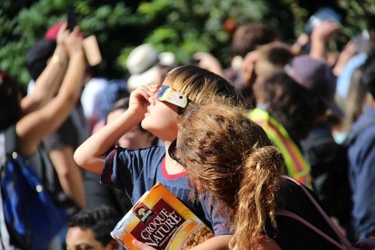 Kid viewing solar eclipse protecting his eyes
