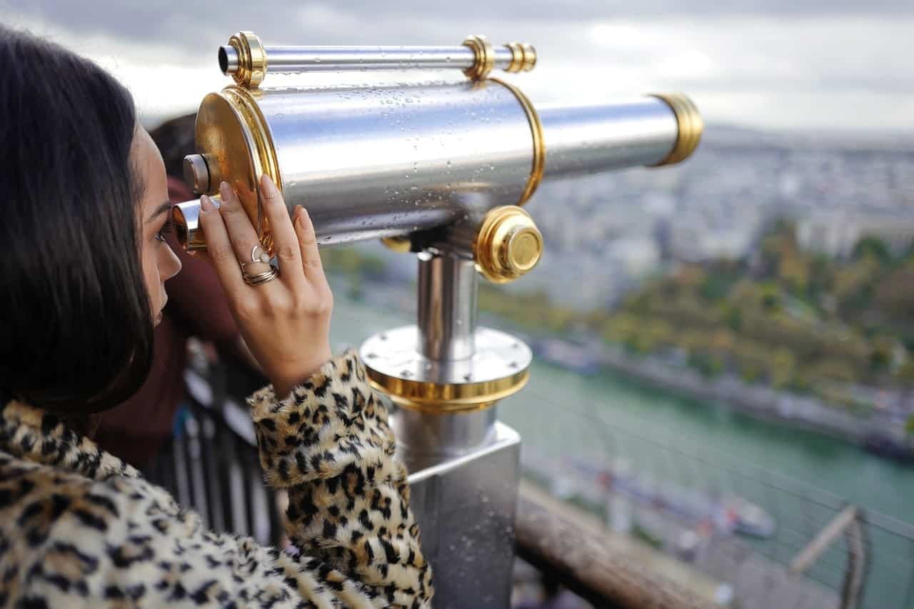 Woman peeping through telescope