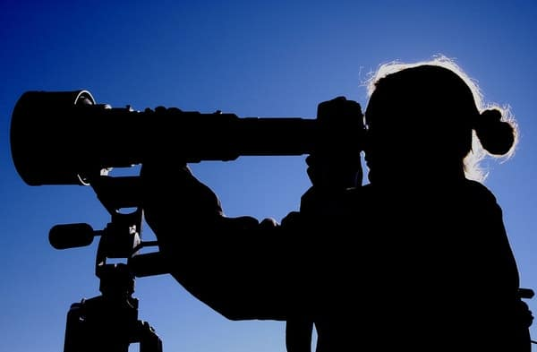 Silhouette image of person looking through telescope