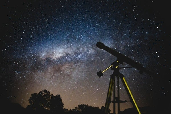 Photo of a telescope at night with stars